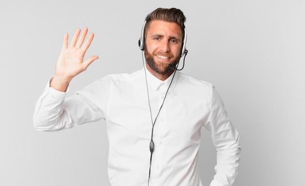 Młody przystojny mężczyzna uśmiecha się radośnie, machając ręką, witając cię i pozdrawiając. koncepcja telemarketingu