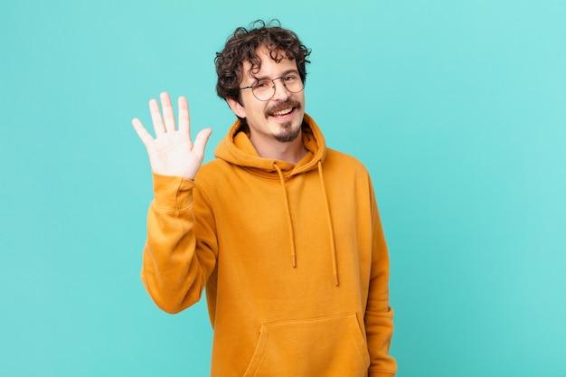 Młody przystojny mężczyzna uśmiecha się radośnie, machając ręką, witając cię i pozdrawiając