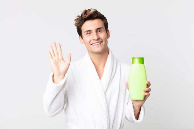 Młody przystojny mężczyzna uśmiecha się radośnie, machając ręką, witając i witając cię szlafrokiem i trzymając butelkę szamponu