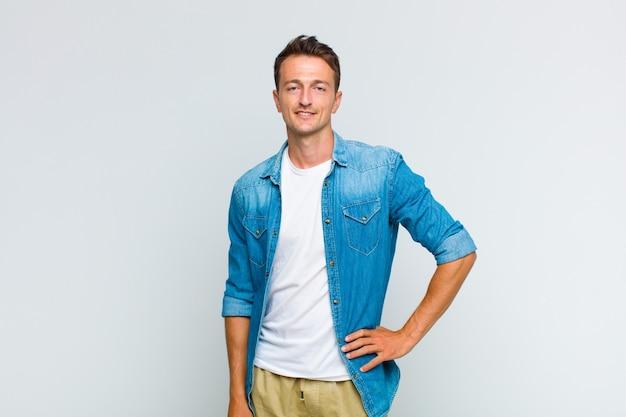 Młody przystojny mężczyzna uśmiecha się radośnie z ręką na biodrze i pewną siebie, pozytywną, dumną i przyjazną postawą