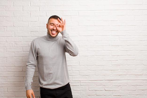 Młody przystojny mężczyzna uśmiecha się radośnie ze śmieszną miną, żartuje i patrzy przez wizjer, szpiegując tajemnice na płaskiej ścianie