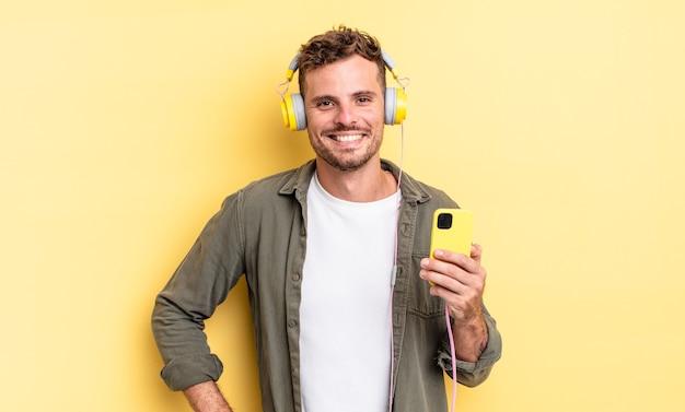Młody przystojny mężczyzna uśmiecha się szczęśliwie z ręką na biodrze i pewnie słuchawki i koncepcja smartfona