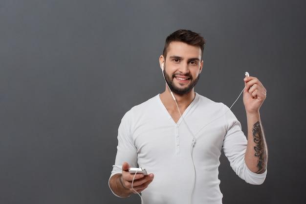 Młody przystojny mężczyzna uśmiecha się trzymając telefon na szarej ścianie