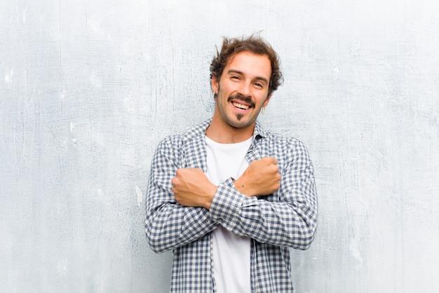 Młody przystojny mężczyzna uśmiecha się wesoło i świętuje, z zaciśniętymi pięściami i skrzyżowanymi rękami, czując się szczęśliwy i pozytywnie ponad ścianą