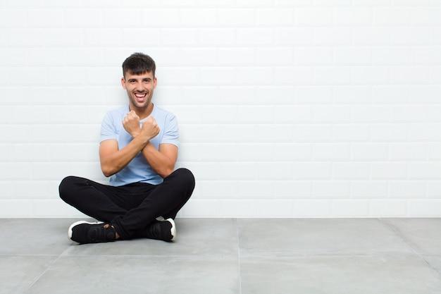 Młody przystojny mężczyzna uśmiecha się wesoło i świętuje, z zaciśniętymi pięściami i skrzyżowanymi rękami, czując się szczęśliwy i pozytywnie siedzący na cementowej podłodze