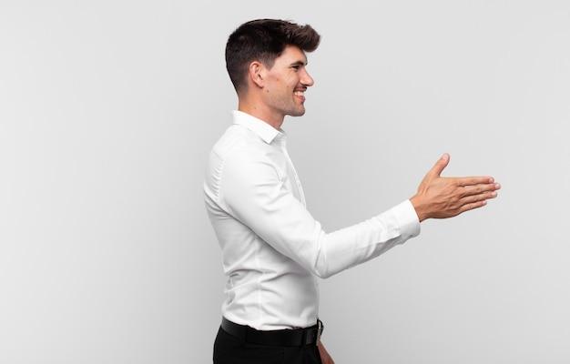 Młody przystojny mężczyzna uśmiecha się, wita i oferuje uścisk dłoni, aby zamknąć udaną transakcję, koncepcja współpracy
