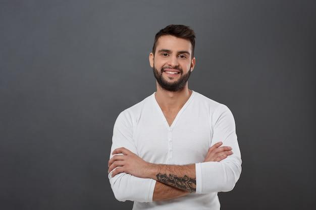 Młody przystojny mężczyzna uśmiecha się ze skrzyżowanymi rękami na szarej ścianie