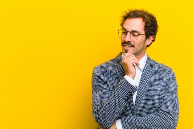 Młody przystojny mężczyzna uśmiecha się ze szczęśliwym, pewnym siebie wyrazem ręki na brodzie, zastanawiając się i patrząc z boku na pomarańczową ścianę