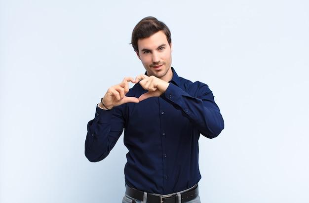 Młody przystojny mężczyzna, uśmiechając się i czując się szczęśliwy, uroczy, romantyczny i zakochany, tworząc kształt serca obiema rękami na niebieskiej ścianie