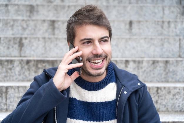 Młody przystojny mężczyzna, uśmiechając się, rozmawia przez telefon, siedząc na schodach.