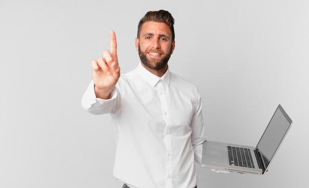 Młody przystojny mężczyzna uśmiechający się dumnie i pewnie robiący numer jeden i trzymający laptopa