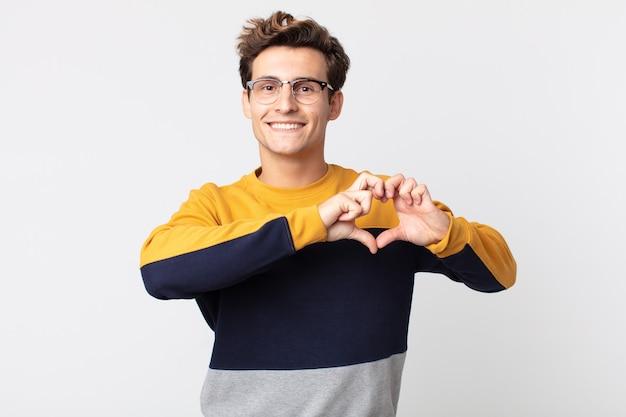 Młody przystojny mężczyzna uśmiechający się i czujący się szczęśliwy, uroczy, romantyczny i zakochany, tworząc kształt serca obiema rękami
