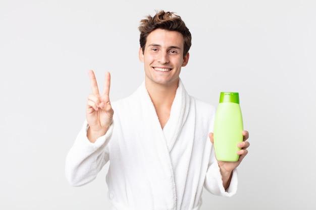 Młody przystojny mężczyzna uśmiechający się i wyglądający na szczęśliwego, gestykulujący zwycięstwo lub pokój w szlafroku i trzymający butelkę szamponu