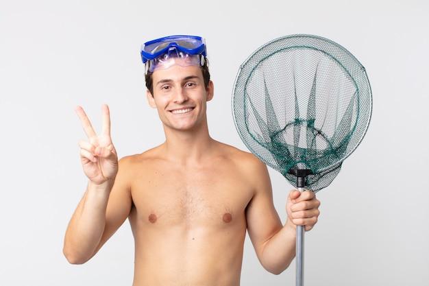Młody przystojny mężczyzna uśmiechający się i wyglądający na szczęśliwego, gestykulujący zwycięstwo lub pokój za pomocą okularów i sieci rybackiej