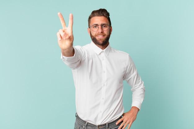 Młody przystojny mężczyzna uśmiechający się i wyglądający na szczęśliwego, gestykulujący zwycięstwo lub pokój