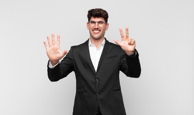 Młody przystojny mężczyzna uśmiechający się i wyglądający przyjaźnie, pokazujący cyfrę osiem lub ósmą z ręką do przodu, odliczając w dół