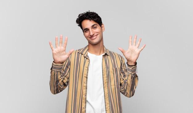 Młody przystojny mężczyzna uśmiechający się i wyglądający przyjaźnie, pokazujący liczbę dziesięć lub dziesiątą ręką do przodu, odliczając w dół
