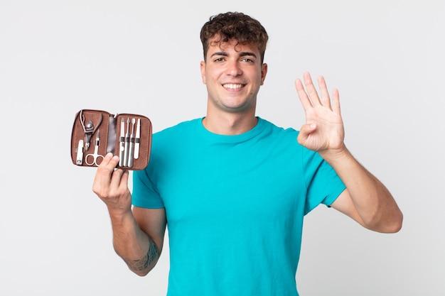 Młody przystojny mężczyzna uśmiechający się i wyglądający przyjaźnie, pokazujący numer cztery i trzymający walizkę z narzędziami do paznokci