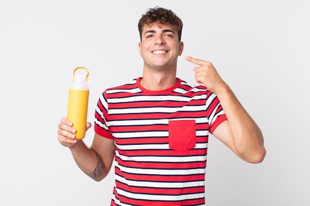 Młody przystojny mężczyzna uśmiechający się pewnie wskazując na swój szeroki uśmiech i trzymający termos z kawą