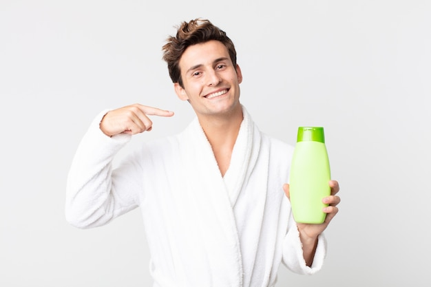Młody przystojny mężczyzna uśmiechający się pewnie wskazując na swój szeroki uśmiech w szlafroku i trzymający butelkę szamponu