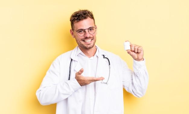 Młody przystojny mężczyzna uśmiechający się radośnie, czując się szczęśliwy i pokazując koncepcję. koncepcja butelki pigułki lekarza