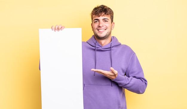 Młody przystojny mężczyzna uśmiechający się radośnie, czując się szczęśliwy i pokazując koncepcję. kopia koncepcja przestrzeni