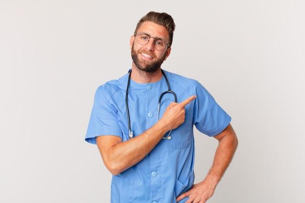 Młody przystojny mężczyzna uśmiechający się radośnie, czując się szczęśliwy i wskazując na bok. koncepcja pielęgniarki