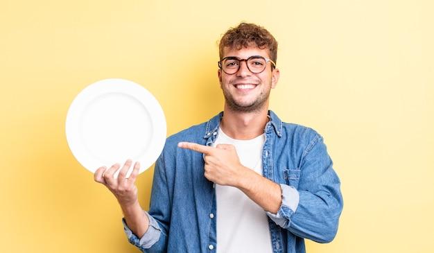 Młody przystojny mężczyzna uśmiechający się radośnie, czując się szczęśliwy i wskazując na bok. koncepcja pustego naczynia