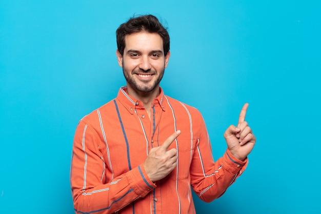 Młody przystojny mężczyzna uśmiechający się radośnie i wskazujący na bok i do góry obiema rękami pokazującymi obiekt w przestrzeni kopii