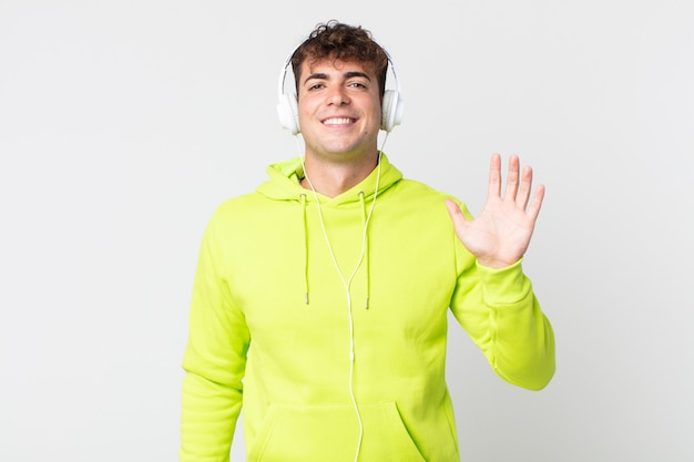 Młody przystojny mężczyzna uśmiechający się radośnie, machający ręką, witający i witający ciebie i słuchawki