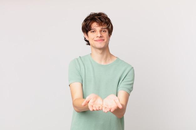 Młody przystojny mężczyzna uśmiechający się radośnie z przyjaznym, oferującym i pokazującym koncepcję