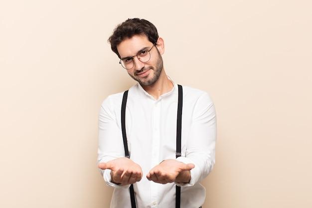 Młody przystojny mężczyzna uśmiechający się radośnie z przyjaznym, pewnym siebie, pozytywnym spojrzeniem, oferujący i pokazujący przedmiot lub koncepcję