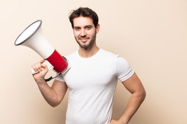 Młody przystojny mężczyzna uśmiechający się radośnie z ręką na biodrze i pewny siebie, pozytywny, dumny i przyjazny