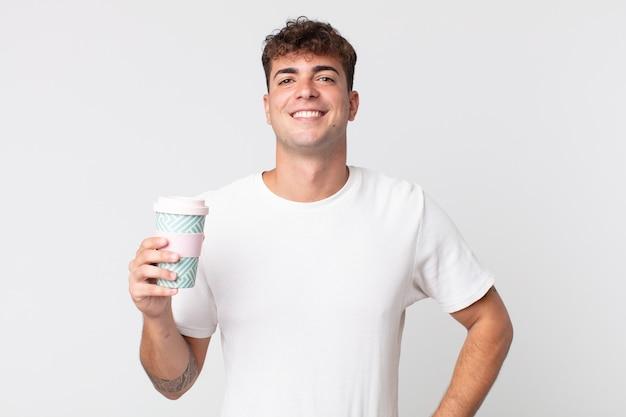 Młody przystojny mężczyzna uśmiechający się radośnie z ręką na biodrze i pewny siebie, trzymający kawę na wynos