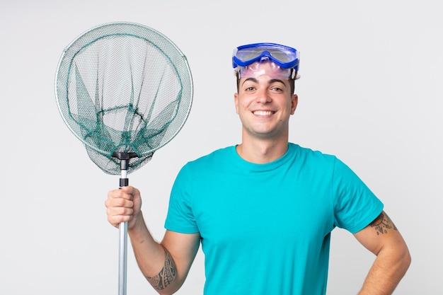 Młody przystojny mężczyzna uśmiechający się radośnie z ręką na biodrze i pewny siebie w okularach i sieci rybackiej