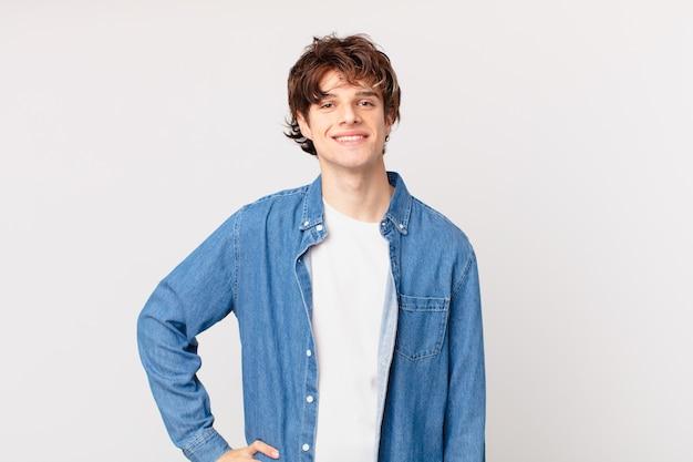 Młody przystojny mężczyzna uśmiechający się radośnie z ręką na biodrze i pewny siebie
