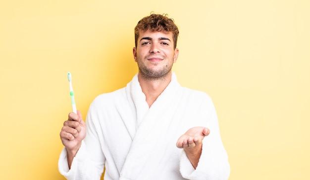 Młody przystojny mężczyzna uśmiechający się szczęśliwie z przyjazną i oferującą i pokazującą koncepcję. koncepcja szczoteczki do zębów