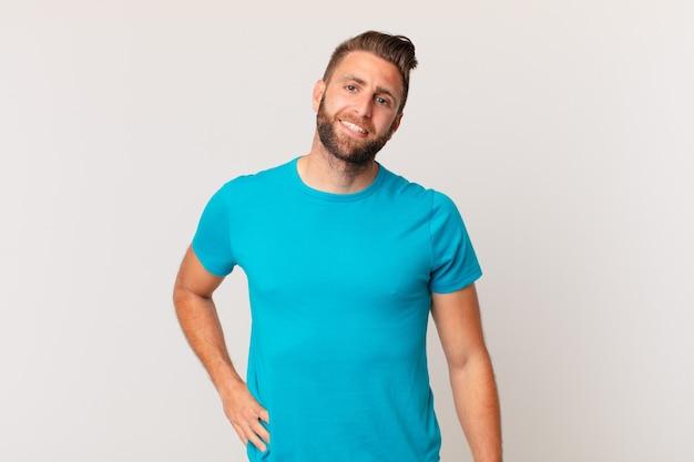 Młody przystojny mężczyzna uśmiechający się szczęśliwie z ręką na biodrze i pewny siebie. koncepcja fitness