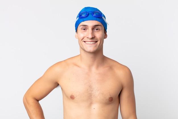 Młody przystojny mężczyzna uśmiechający się szczęśliwie z ręką na biodrze i pewny siebie. koncepcja pływaka