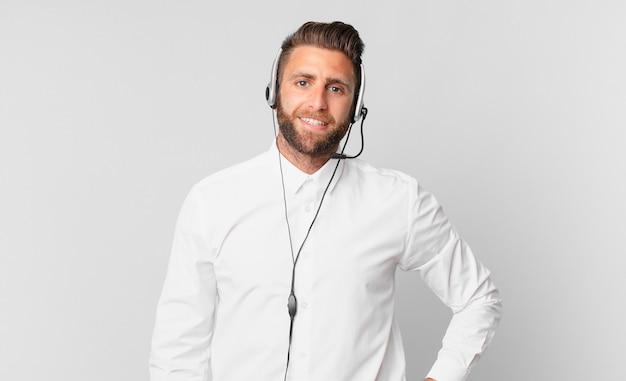 Młody przystojny mężczyzna uśmiechający się szczęśliwie z ręką na biodrze i pewny siebie. koncepcja telemarketingu