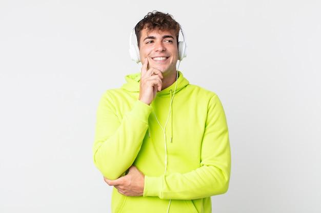 Młody przystojny mężczyzna uśmiechający się ze szczęśliwym, pewnym siebie wyrazem twarzy z ręką na brodzie i słuchawkami