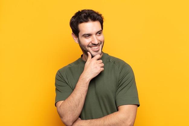 Młody przystojny mężczyzna uśmiechający się ze szczęśliwym, pewnym siebie wyrazem twarzy z ręką na brodzie, zastanawiający się i patrzący w bok