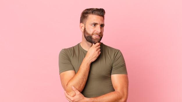 Młody przystojny mężczyzna uśmiechający się ze szczęśliwym, pewnym siebie wyrazem twarzy z ręką na brodzie