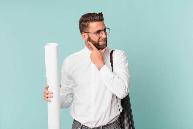 Młody przystojny mężczyzna uśmiechający się ze szczęśliwym, pewnym siebie wyrazem z ręką na brodzie. koncepcja architekta