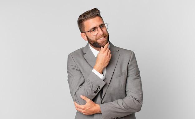 Młody przystojny mężczyzna uśmiechający się ze szczęśliwym, pewnym siebie wyrazem z ręką na brodzie. pomysł na biznes