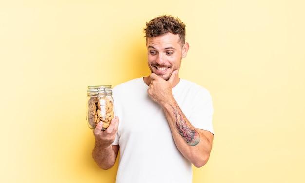 Młody przystojny mężczyzna uśmiechający się ze szczęśliwym, pewnym siebie wyrazem z ręką na koncepcji butelki ciasteczek podbródka