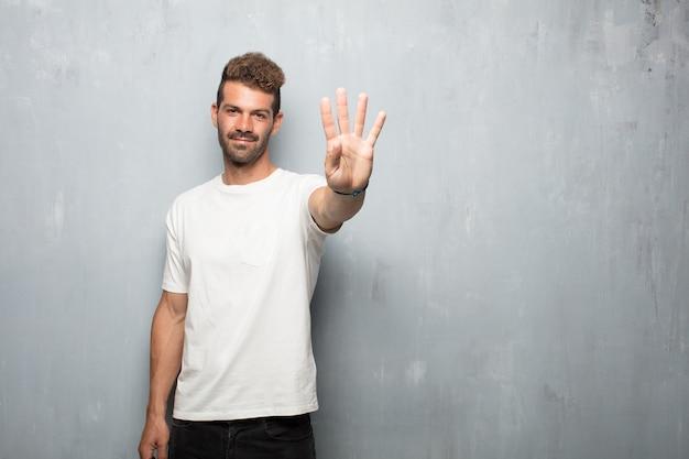 Młody przystojny mężczyzna uśmiechnięty i patrzeje zadowolony i szczęśliwy, liczący liczbę cztery z palcami.