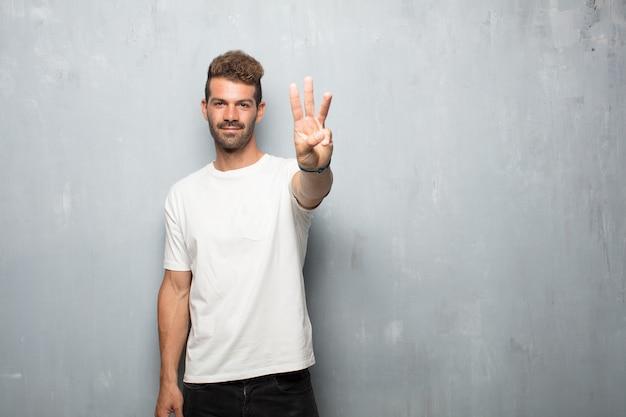 Młody przystojny mężczyzna uśmiechnięty i patrzeje zadowolony i szczęśliwy, liczący liczbę trzy z palcami.