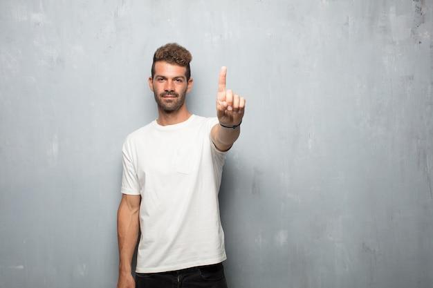 Młody przystojny mężczyzna uśmiechnięty i patrzeje zadowolony i szczęśliwy, liczący liczbę z jeden palcem.