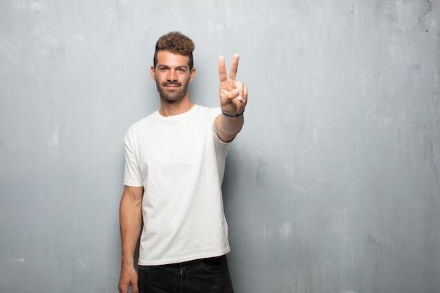 Młody przystojny mężczyzna uśmiechnięty i patrzeje zadowolony i szczęśliwy, liczący numer dwa z palcami.